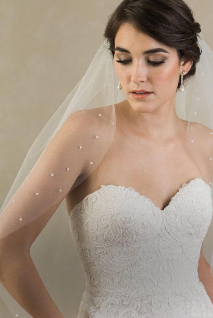 Model wearing Lii Bridal accessories that include a veil and earrings