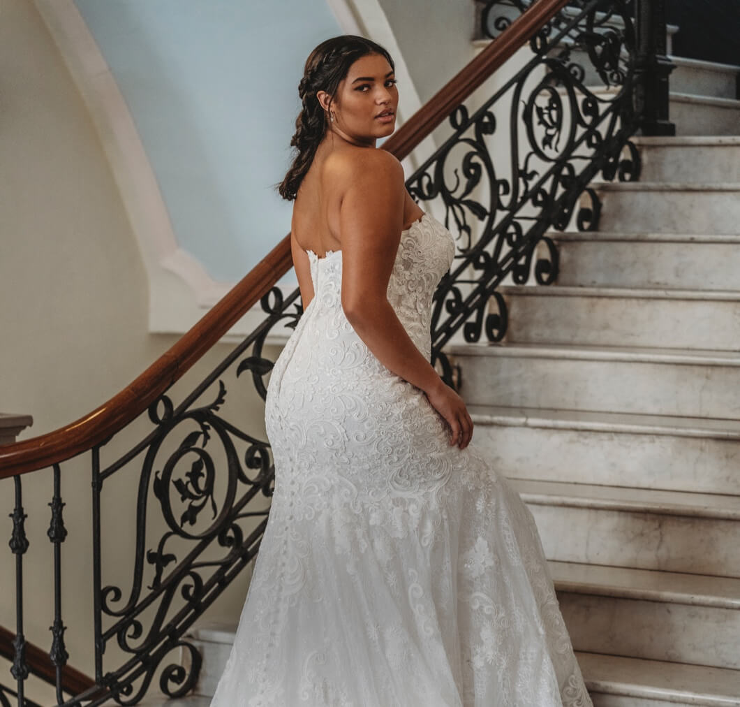 Plus-size Model in a wedding gown walking up stairs