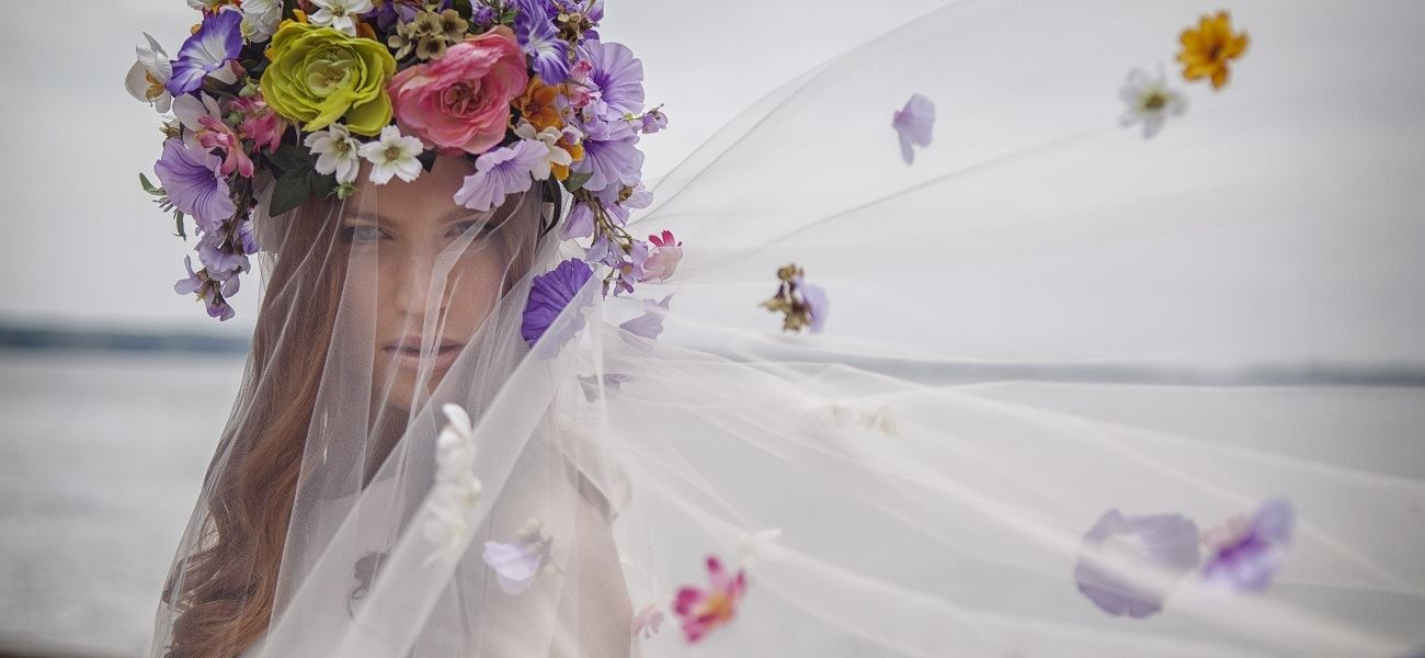 Bride Wearing A Large Flower Crown Featuring Purple And Pink Flowers. Veil Is Under The Flower Crown.